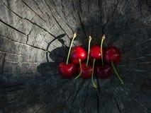 Duas fileiras de cerejas doces em uma superfície de madeira Fotografia de Stock Royalty Free