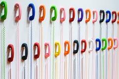 Duas fileiras dos monofones coloridos estão pendurando em uma parede branca fios Imagem de Stock