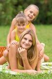 Duas filhas estão sentando-se na mãe nova, que se está encontrando na grama verde Imagens de Stock Royalty Free