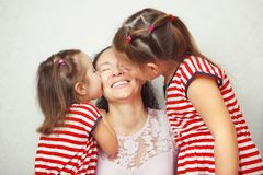 Duas filhas pequenas beijam sua mãe nos mordentes Foto de Stock