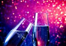 Duas flautas de champanhe com ouro borbulham no fundo azul do bokeh da luz do matiz Foto de Stock