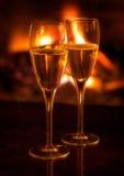 Duas flautas de champanhe leves pelo incêndio de registro Fotos de Stock Royalty Free