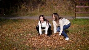 Duas folhas douradas do lance bonito da mulher no outono jardinam As meninas saltam, têm o divertimento, ato como crianças movime filme