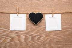 Duas fotos imediatas vazias com coração no fundo de madeira Foto de Stock