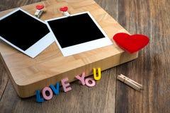 Duas fotos imediatas vazias com corações vermelhos No fundo de madeira Imagem de Stock Royalty Free