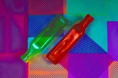 Duas garrafas coloridas em um fundo geométrico abstrato Imagem de Stock Royalty Free