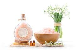 Duas garrafas com óleo essencial orgânico com as flores frescas do snowdrop, sabão, sal Himalaia no fundo de madeira e branco vel Fotografia de Stock Royalty Free
