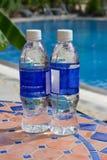 Duas garrafas da água transparente estão em uma tabela pequena de um mosaico Imagem de Stock