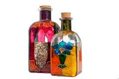 Duas garrafas do vidro colorido com um interior da cortiça e da areia no fundo branco isolado perto acima na luz solar com sombra fotos de stock
