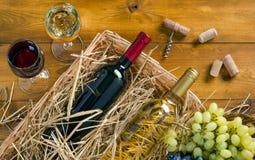 Duas garrafas, vidros do vinho, grupos de uvas na tabela de madeira imagem de stock royalty free