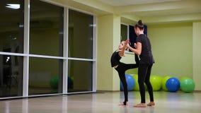 Duas ginastas art?sticas das irm?s bonitos magros das meninas no sportswear preto para fazer o aquecimento no gym e para executar video estoque