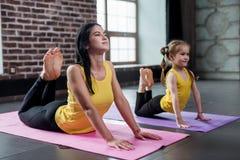 Duas ginastas fêmeas da idade diferente que fazem esticando o exercício que arqueia para trás a tentativa tocar na cabeça com for Imagens de Stock