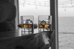 Duas goles do uísque nas rochas na cornija de lareira da chaminé Foto de Stock