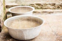 Duas grandes bacias de alumínio velhas da água estão na terra fotos de stock royalty free