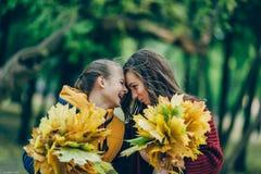Duas irmãs abraçam, com um grupo das folhas no parque Fotografia de Stock