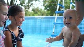 Duas irmãs adolescentes jogam com seu irmão mais novo na associação, água ele com alguma água O bebê de um ano banha-se dentro vídeos de arquivo