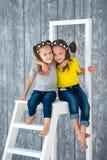 Duas irmãs alegres bonitas das meninas nas calças de brim estão sentando-se em uma escada portátil na frente de um fundo de madei fotografia de stock royalty free