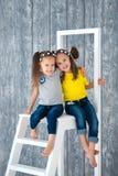 Duas irmãs alegres bonitas das meninas nas calças de brim estão sentando-se em uma escada portátil na frente de um fundo de madei imagem de stock