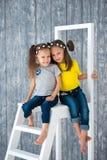 Duas irmãs alegres bonitas das meninas nas calças de brim estão sentando-se em uma escada portátil na frente de um fundo de madei imagens de stock