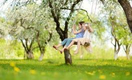 Duas irmãs bonitos que têm o divertimento em um balanço no jardim velho de florescência da árvore de maçã fora no dia de mola ens fotos de stock royalty free