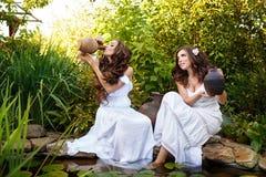 Duas irmãs com lagoa dos jarros Fotos de Stock Royalty Free