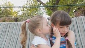 Duas irmãs compartilham de um segredo em um balanço no jardim, sussurro em sua orelha filme