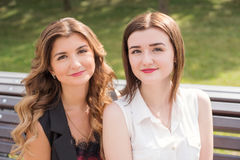 Duas irmãs da jovem mulher que sentam-se em um banco em um parque Fotografia de Stock