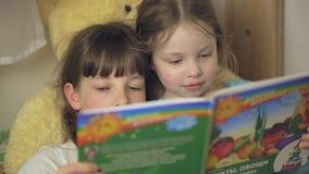 Duas irmãs das meninas estão lendo um livro ao encontrar-se na cama na sala de crianças filme