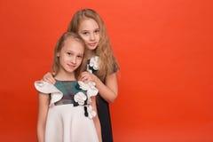 Duas irmãs em vestidos estilizados bonitos em um fundo vermelho dentro Imagem de Stock Royalty Free