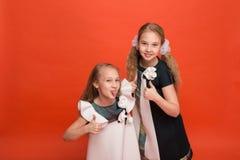 Duas irmãs em vestidos estilizados bonitos em um fundo vermelho dentro Imagens de Stock
