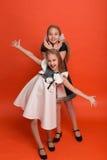 Duas irmãs em vestidos estilizados bonitos em um fundo vermelho dentro Fotografia de Stock