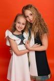 Duas irmãs em vestidos estilizados bonitos em um fundo vermelho dentro Fotos de Stock Royalty Free