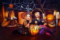Duas irmãs engraçadas bonitos comemoram o feriado As crianças alegres no carnaval trajam pronto para Dia das Bruxas foto de stock royalty free