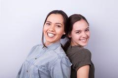 Duas irmãs felizes no fundo cinzento Fotos de Stock