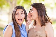 Duas irmãs gêmeas étnicas bonitas que sussurram segredos fora Fotografia de Stock Royalty Free