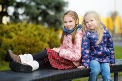 Duas irmãs mais nova adoráveis que abraçam e que afagam fora no dia de mola bonito Foto de Stock