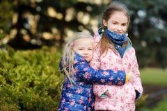 Duas irmãs mais nova adoráveis que abraçam e que afagam fora no dia de mola bonito Imagem de Stock