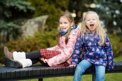 Duas irmãs mais nova adoráveis que abraçam e que afagam fora no dia de mola bonito Imagens de Stock