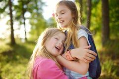 Duas irmãs mais nova adoráveis que abraçam e que afagam fora no dia de verão bonito Fotografia de Stock Royalty Free
