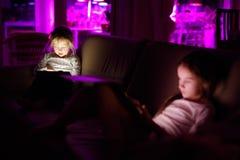 Duas irmãs mais nova adoráveis que jogam com uma tabuleta digital em uma sala escura imagens de stock royalty free