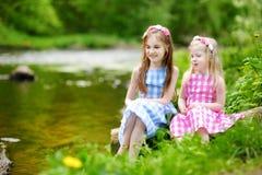 Duas irmãs mais nova adoráveis que jogam por um rio no parque ensolarado Imagem de Stock