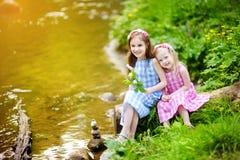 Duas irmãs mais nova adoráveis que jogam por um rio no parque ensolarado Fotografia de Stock