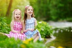 Duas irmãs mais nova adoráveis que jogam por um rio no parque ensolarado em um dia de verão bonito Imagem de Stock