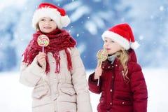 Duas irmãs mais nova adoráveis que vestem os chapéus de Santa que comem pirulitos listrados enormes do Natal no dia de inverno bo Fotografia de Stock