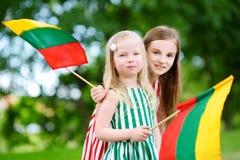 Duas irmãs mais nova bonitas que guardam bandeiras lituanas tricolor Foto de Stock Royalty Free