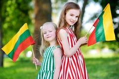 Duas irmãs mais nova bonitas que guardam bandeiras lituanas tricolor Fotos de Stock