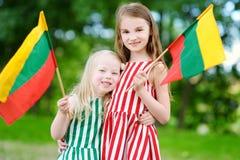 Duas irmãs mais nova bonitas que guardam bandeiras lituanas tricolor Imagem de Stock