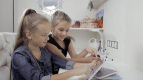 Duas irmãs mais nova bonitas sentam-se em uma tabela e em um jogo em um PC da tabuleta Meninas de sorriso felizes video estoque