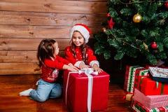 Duas irmãs mais nova bonitos com a caixa de presente atual vermelha grande perto da árvore em casa imagens de stock