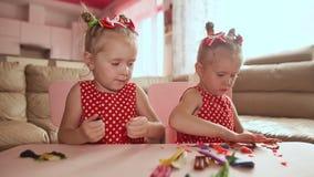 Duas irmãs mais nova bonitos, com prazer junto com a modelagem colorida Crianças criativas em casa Jogo de crianças com vídeos de arquivo